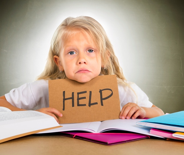 cute little blonde hair school girl sad and frustrated holding help sign in stress with books and homework in children education concept isolated on grunge studio background