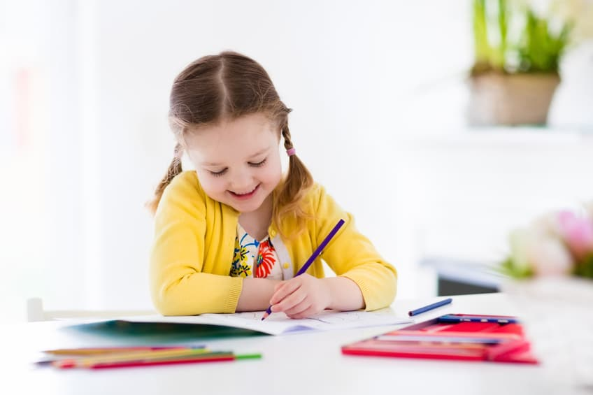 Cute little girl doing homework, reading a book, coloring pages, writing and painting. Children paint. Kids draw. Preschooler with books at home. Preschoolers learn to write and read. Creative toddler